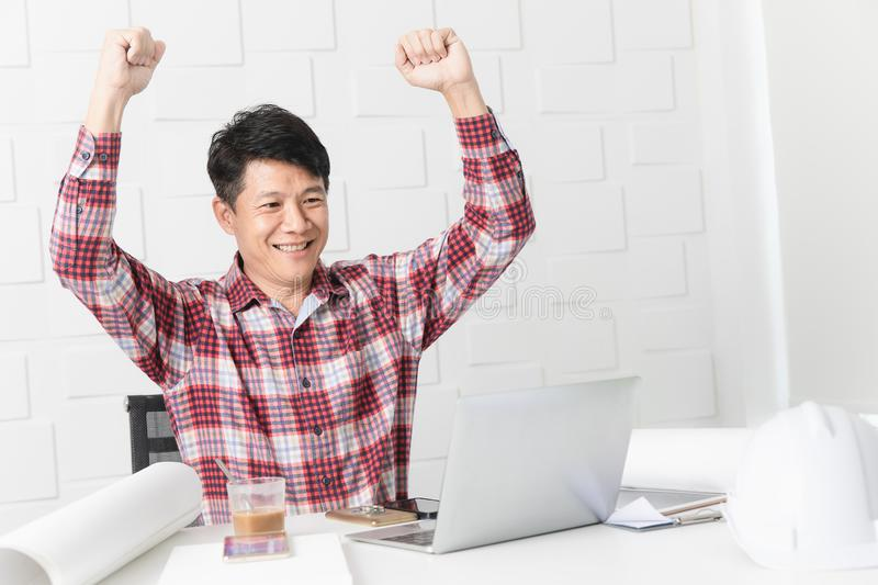 Asian architect at construction site office. Middle aged Asian handsome architect, in checked shirt, working at construction site office, making winner gesture stock photography
