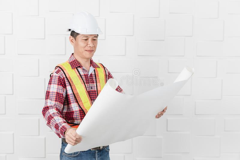 Asian architect at construction site office. Middle aged Asian handsome architect, in jeans and checked shirt, wearing orange, yellow reflective safety vest, and royalty free stock photo