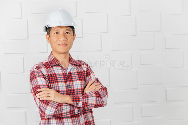 Asian architect at construction site office. Middle aged Asian handsome architect, in jeans and checked shirt, wearing white helmet, standing, cross her arm on royalty free stock photo