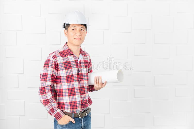 Asian architect at construction site office. Middle aged Asian handsome architect, in jeans and checked shirt, wearing white helmet, standing, use smartphone stock images