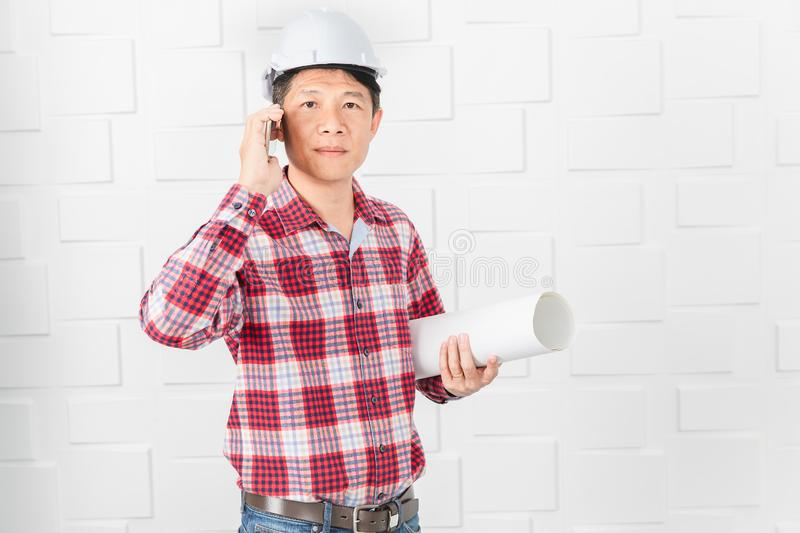Asian architect at construction site office. Middle aged Asian handsome architect, in jeans and checked shirt, wearing white helmet, standing, use smartphone stock image