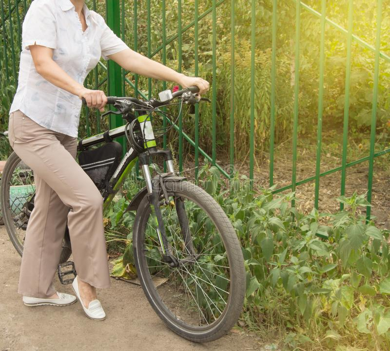 Middle-aged attractive slim woman in light trousers and shirt stands near the bike in the Park on a Sunny summer day, Cycling royalty free stock photos