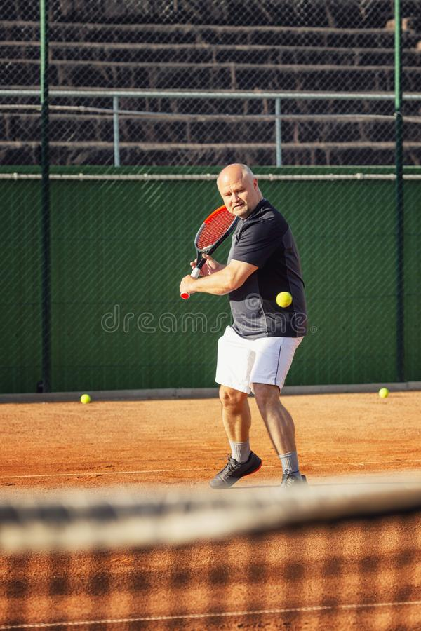 A middle-aged bald man emotionally plays tennis on the court. Outdoor. royalty free stock photos