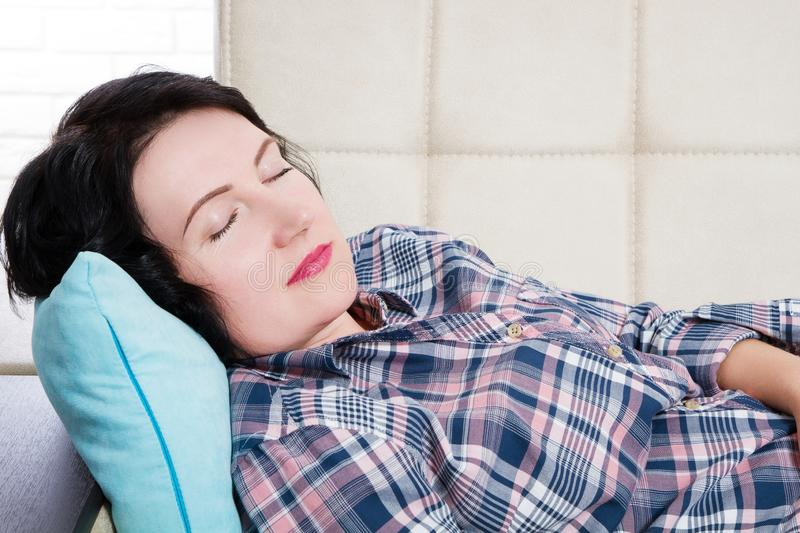 Middle aged beautiful woman lying in sofa sleeping at home after hard working day tired. Sweet dreams, good morning, new day. Weekend, day off, holidays stock images