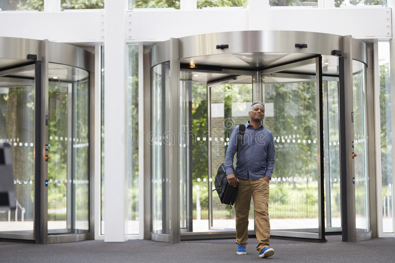Middle aged black man entering the foyer of modern building royalty free stock photos