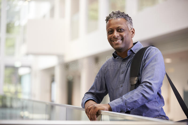 Middle aged black man smiling in modern building lobby royalty free stock images