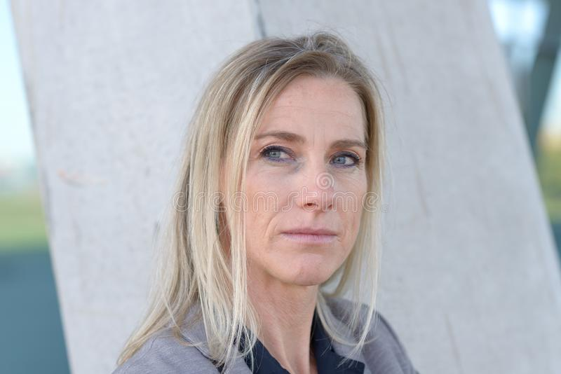 Middle-aged blond woman deep in thought fotografia de stock