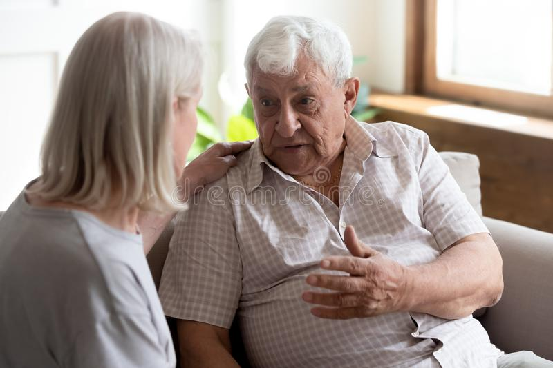 Geriatric nurse listens elderly man showing care and support. Middle-aged blond women put hand on 70s men shoulder attentive listens him and showing care and stock photo