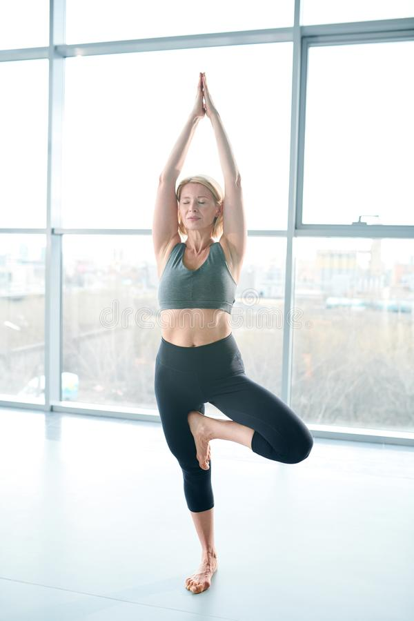 Yoga practice. Middle aged blonde woman in activewear keeping her hands together over head while standing on right leg with the other one bent in knee royalty free stock image