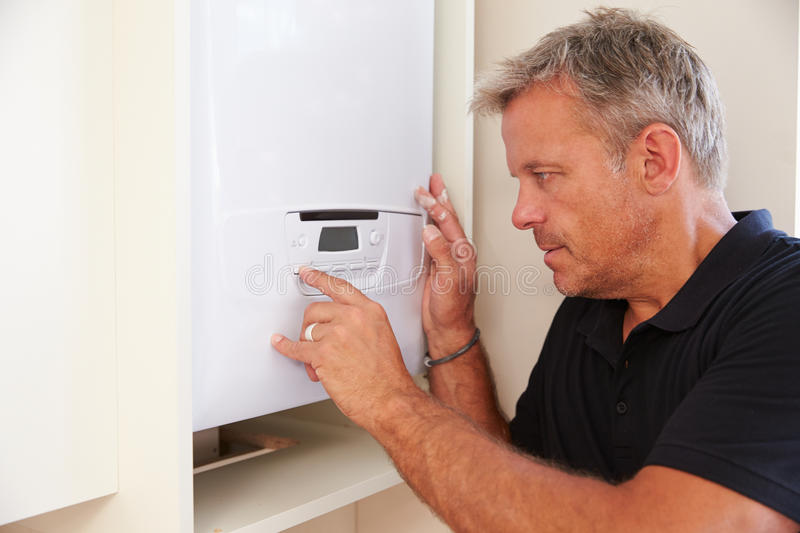 Middle aged boiler technician servicing a domestic boiler royalty free stock photos