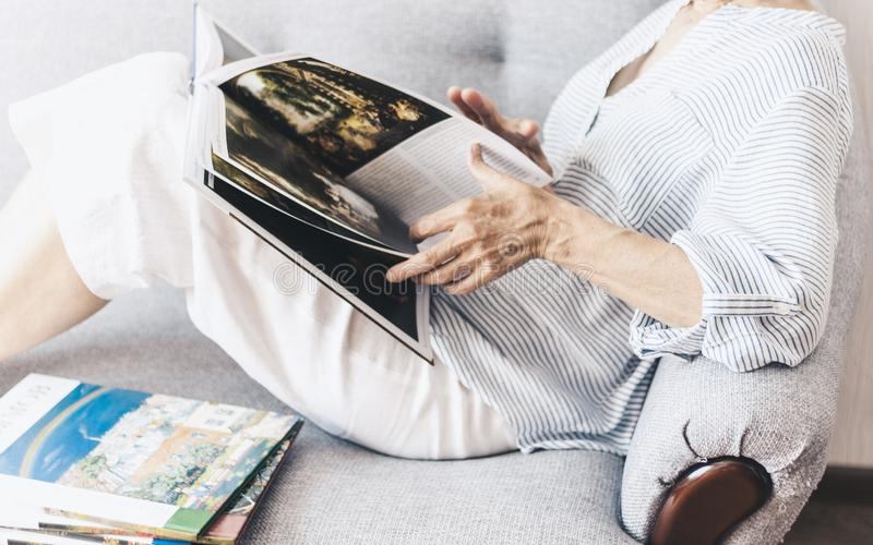 Middle-aged brunette woman on the gray sofa looking at album with paintings by artists royalty free stock photos