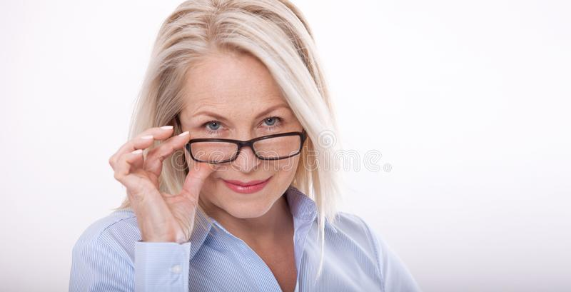 Middle aged business woman with eyeglasses in blue shirt isolated on white background stock image