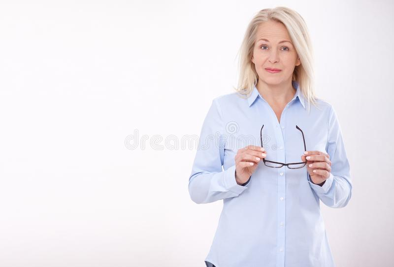 Middle aged business woman with eyeglasses in blue shirt isolated on white background royalty free stock image
