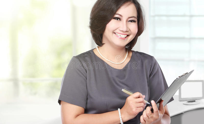 Middle aged Business woman holding a clipboard stock photos
