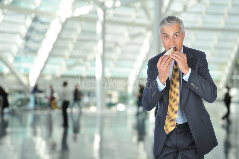 Middle aged Businessman Eating Sandwich stock photo