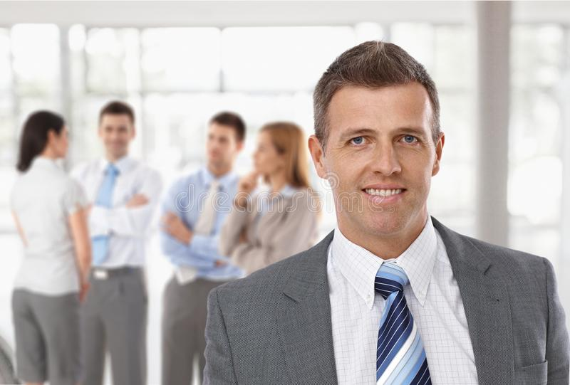 Middle-aged businessman in front of colleagues. Middle-aged businessman in front, business team talking in background stock image