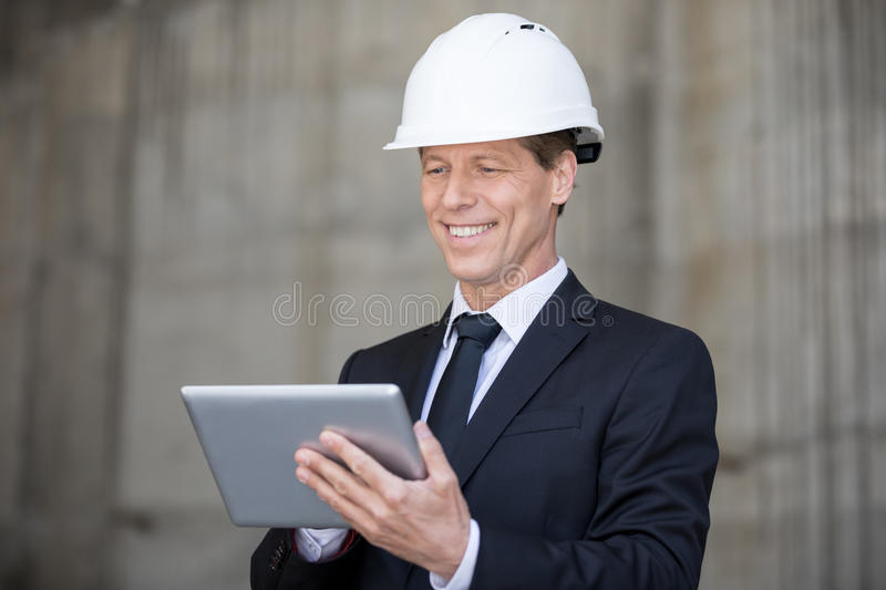 Middle aged businessman in hard hat using digital tablet stock photography