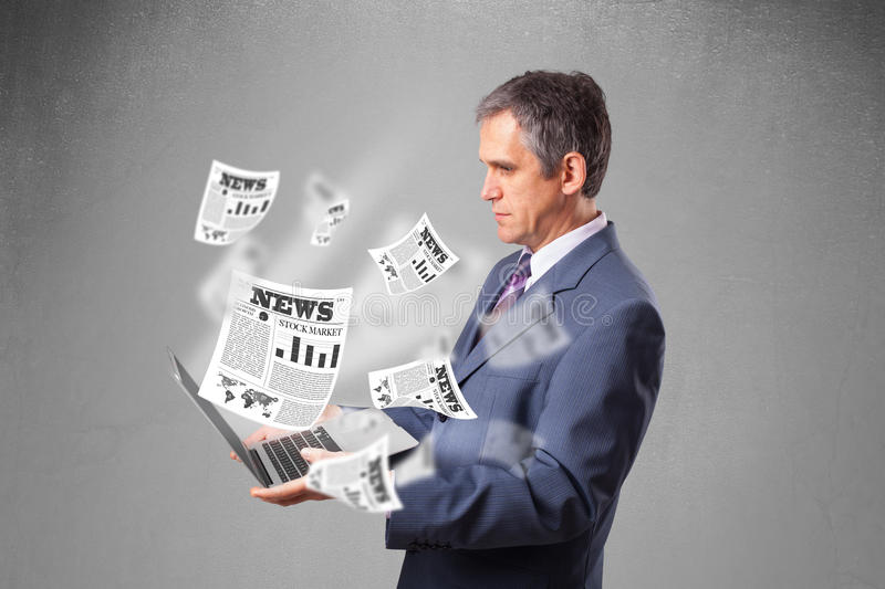 Middle aged businessman holding notebook and reading the explosive newspaper. Handsome middle aged businessman holding notebook and reading the explosive stock image
