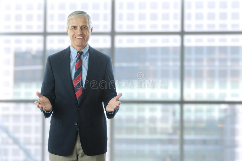 Middle aged Businessman in Lobby Modern Building. Smiling middle aged businessman standing in the lobby of a modern office building. Man is wearing a blue blazer stock images