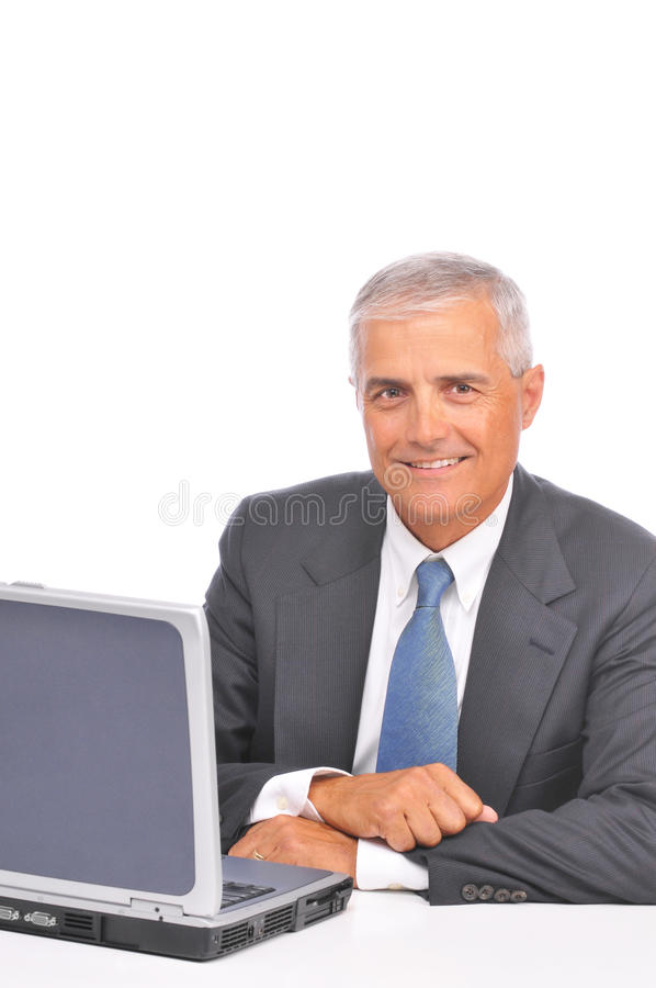 Middle aged Businessman looking over top of laptop stock photo