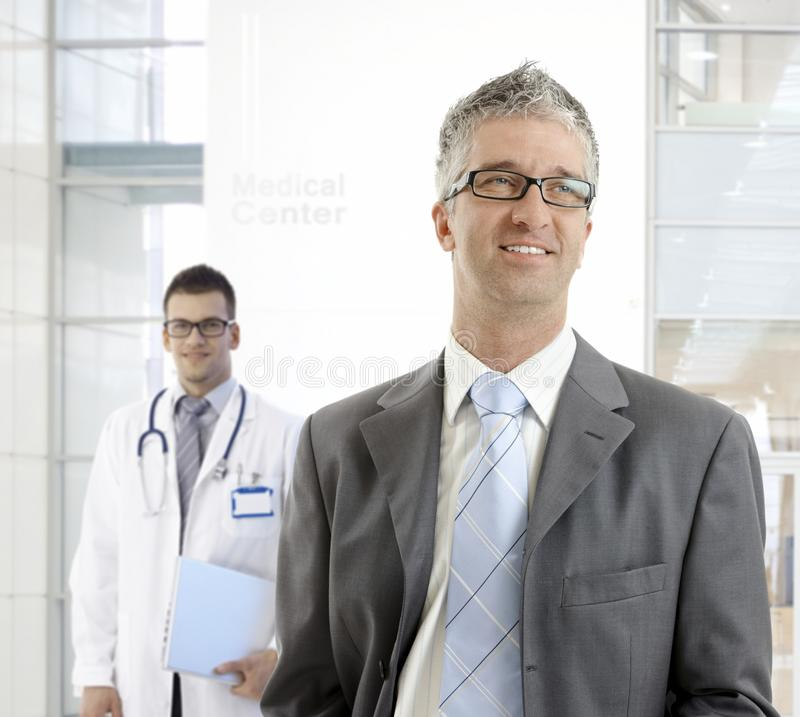 MIddle-aged businessman at medical center. MIddle-aged businessman standing at medical center, smiling, looking away royalty free stock images
