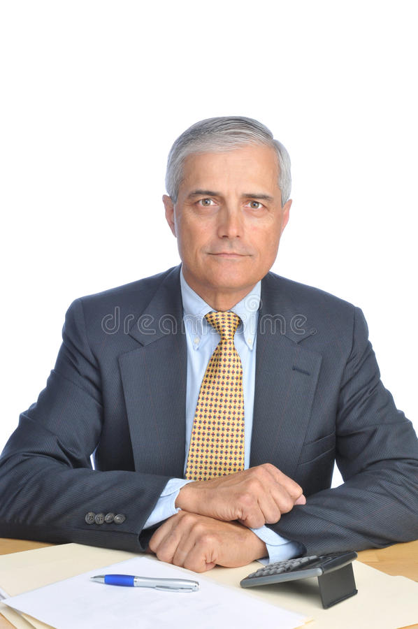Middle aged Businessman seated at Desk royalty free stock image