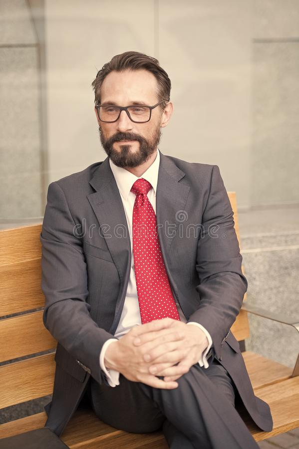 Middle-aged businessman taking a relaxing break on bench. City Life Series of business persons. Portrait of a businessman sitting stock photography