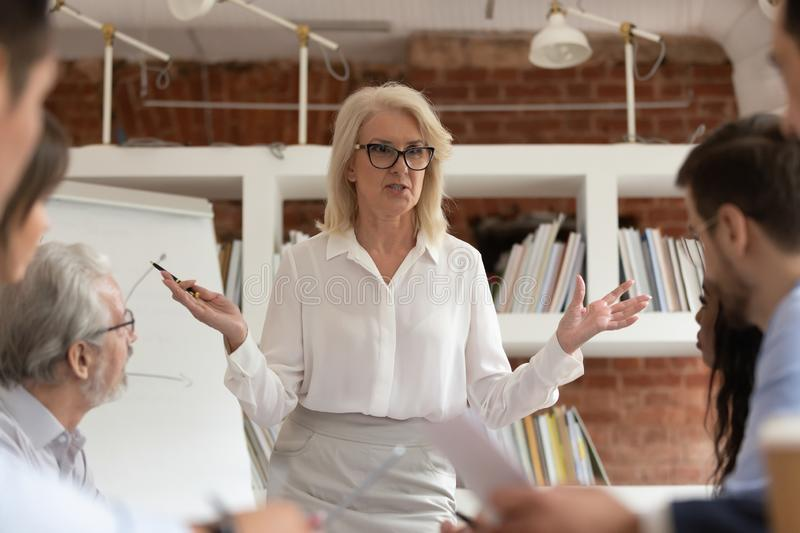 Middle-aged businesswoman head company briefing with colleagues. Middle-aged businesswoman stand talking with diverse colleagues heading company office briefing stock images