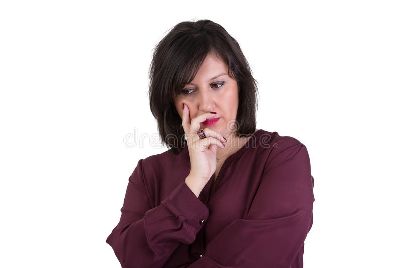 Middle Aged Businesswoman Looking down Thoughtfully. Middle Aged Businesswoman in shirt looking down thoughtfully with her hand on her face royalty free stock image