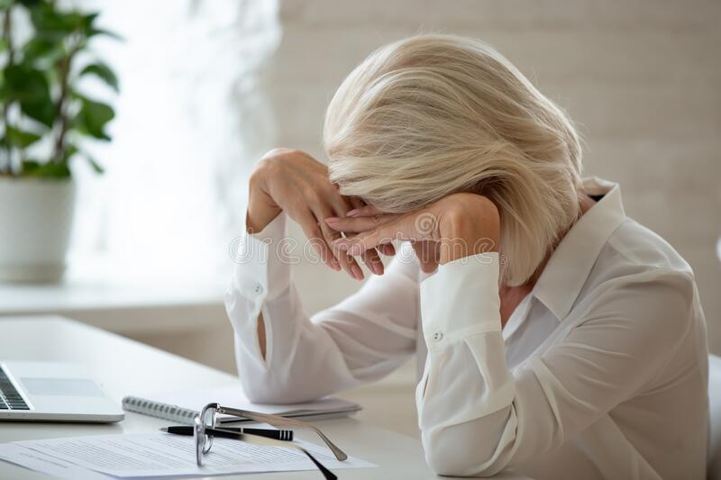 Middle-aged businesswoman lowered head over workplace desk feels unhealthy. Middle-aged businesswoman took off eyeglasses lowered head over workplace desk feels stock photography