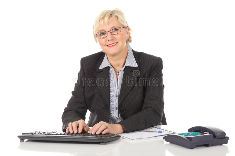 Middle aged businesswoman at office. Attractive middle aged caucasian businesswoman in office with telephone and notebook, typing on keyboard. Studio shot. White royalty free stock photography