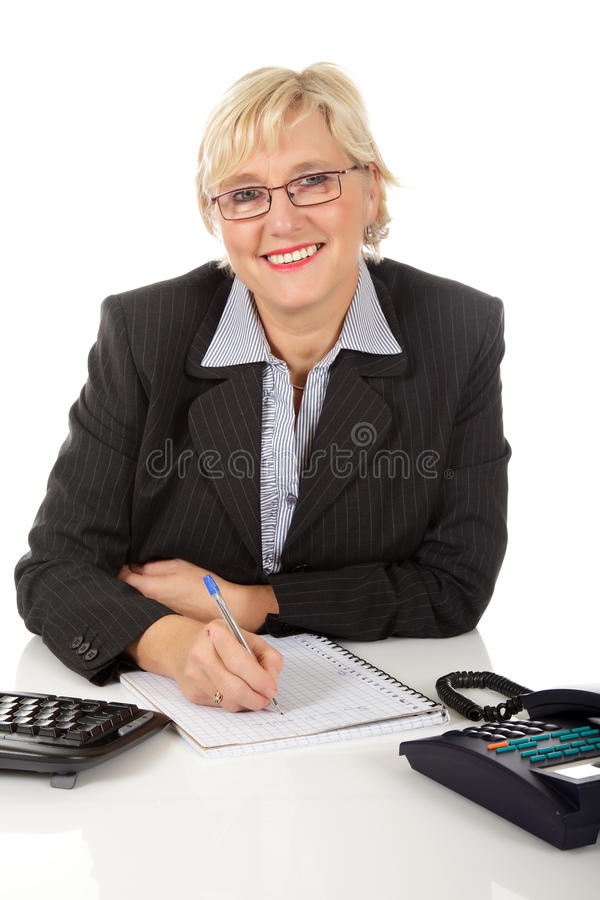 Middle aged businesswoman at office. Attractive middle aged caucasian businesswoman in office with telephone and keyboard on her desk, writing on a notebook stock images