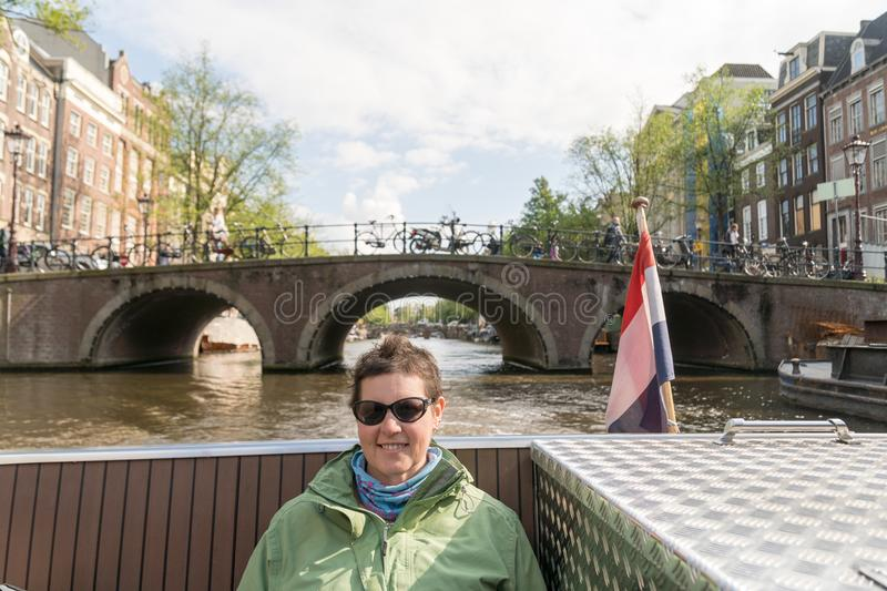 Middle Aged Woman on Canal Boat in Amsterdam royalty free stock photos