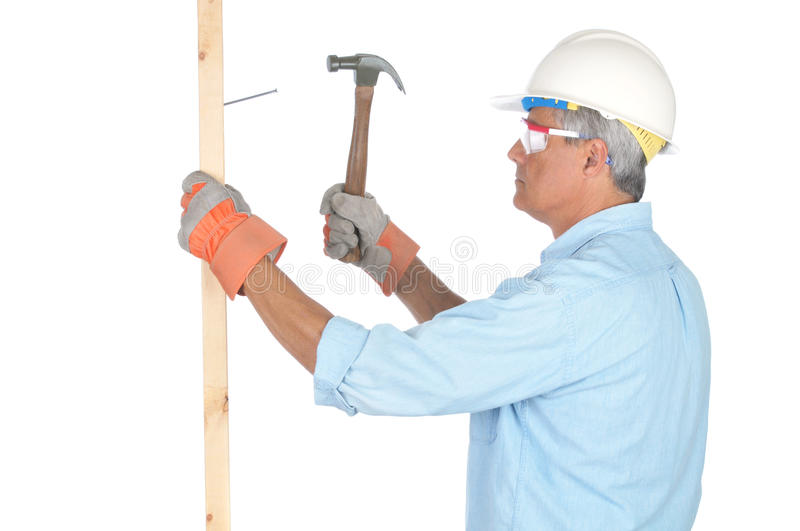 Middle aged Construction Worker With Hammer. Middle aged Construction Worker Hammering Nail into Board side view isolated on white royalty free stock photos