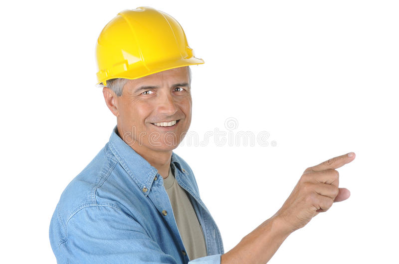 Middle aged Construction Worker Pointing. Middle aged Construction worker wearing a yellow hard hat pointing while he smiles at the camera. Closeup in horizontal royalty free stock photography
