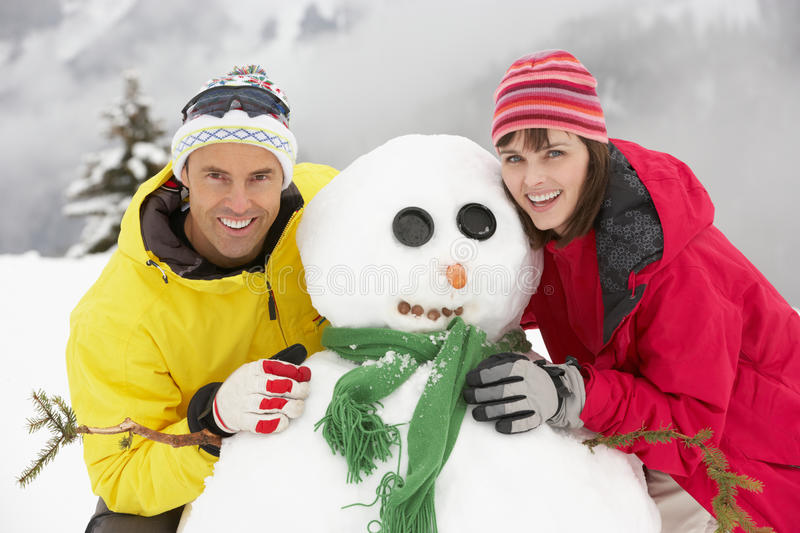 Middle Aged Couple Building Snowman On Ski Holiday