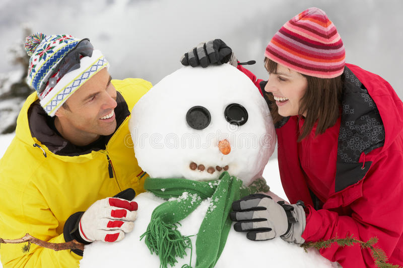 Download Middle Aged Couple Building Snowman On Ski Holiday Stock Photography - Image: 25645152