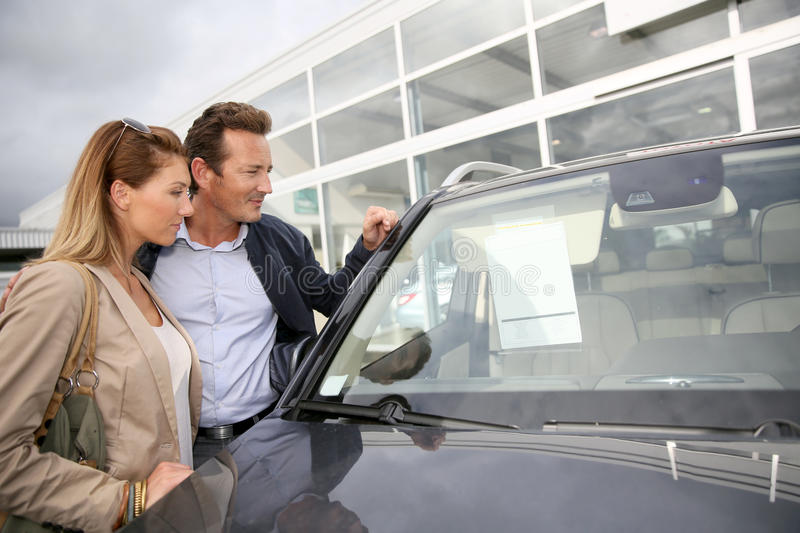 Middle-aged couple buying new car royalty free stock photo