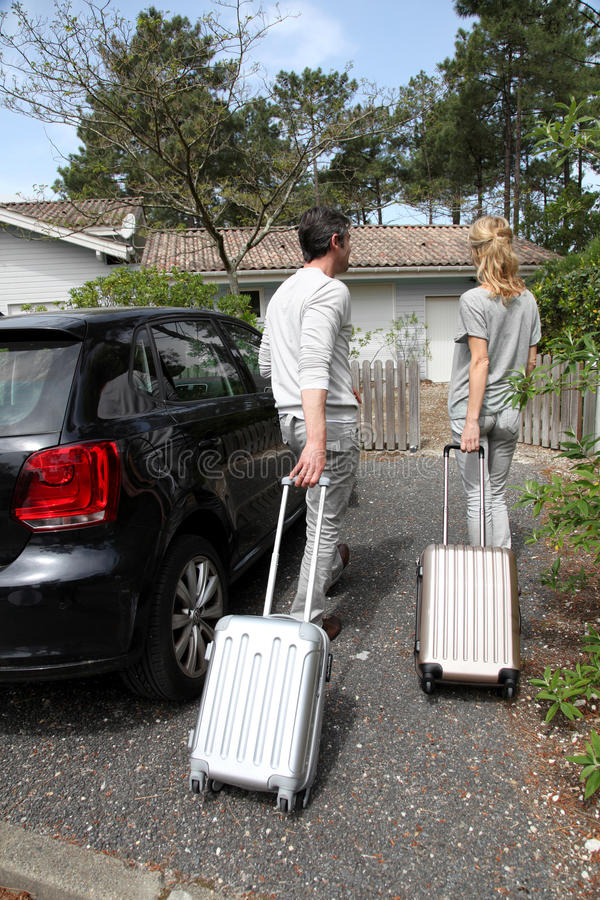 Middle-aged couple coming home from holidays stock photo