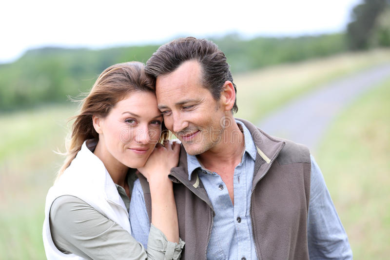 Middle-aged couple on countryside feeling serene stock photo