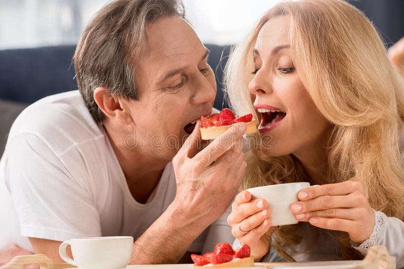Middle aged couple having breakfast together in bed stock image