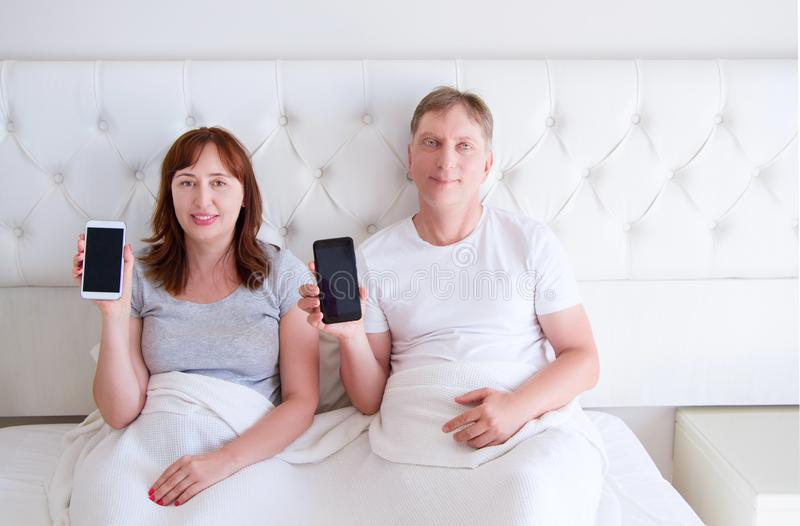 Middle aged couple holding blank screen mobile phone and lying on bed in hotel room bedroom royalty free stock images