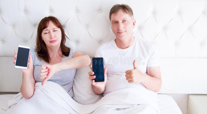 Middle aged couple holding blank screen mobile phone and lying on bed in hotel room bedroom stock photo