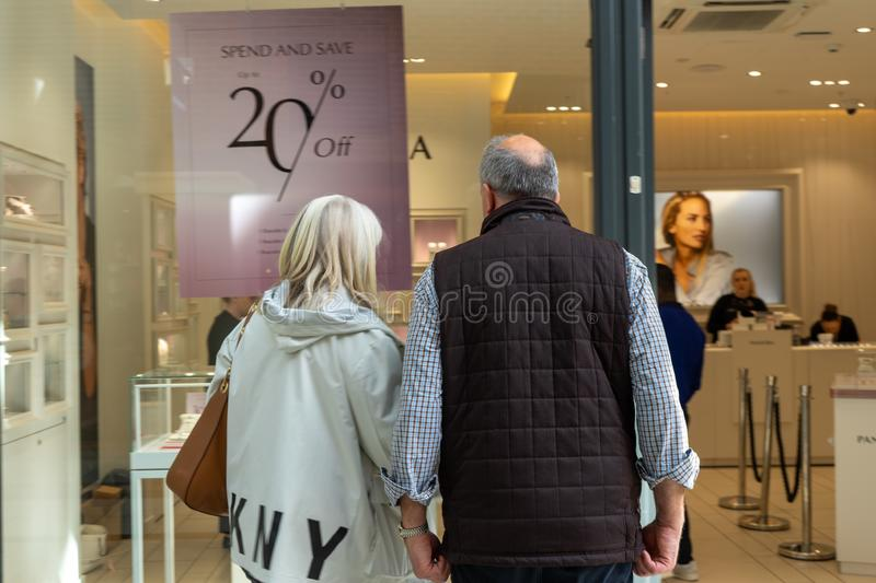 A middle aged couple looking in a shop window at goods for sale stock photography