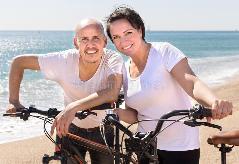 Middle-aged man and woman with bicycles walking on the beach. Middle-aged couple of men and women with bicycles walking on the beach stock photos