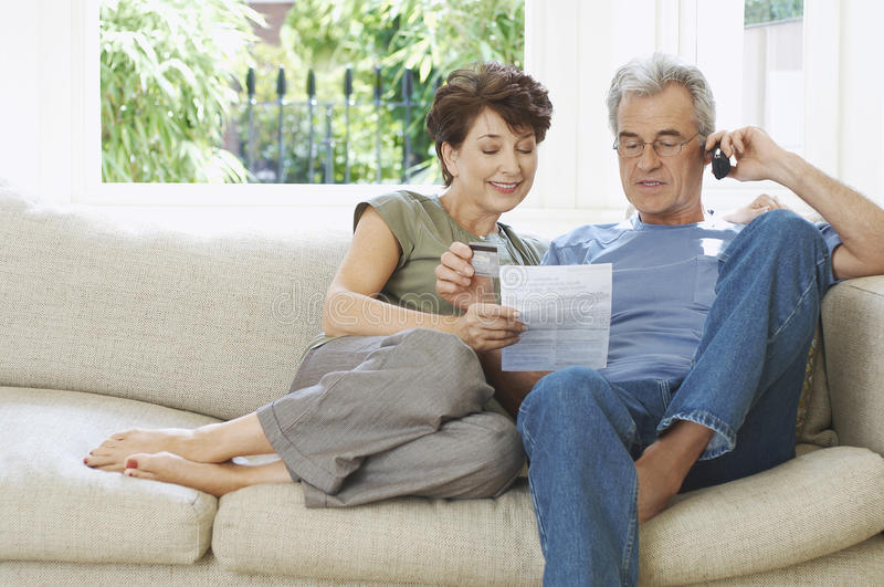 Middle Aged Couple Paying Bill By Phone. On couch at home royalty free stock image
