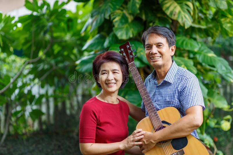 Middle aged  couple playing guitar while relax in backyard stock photos