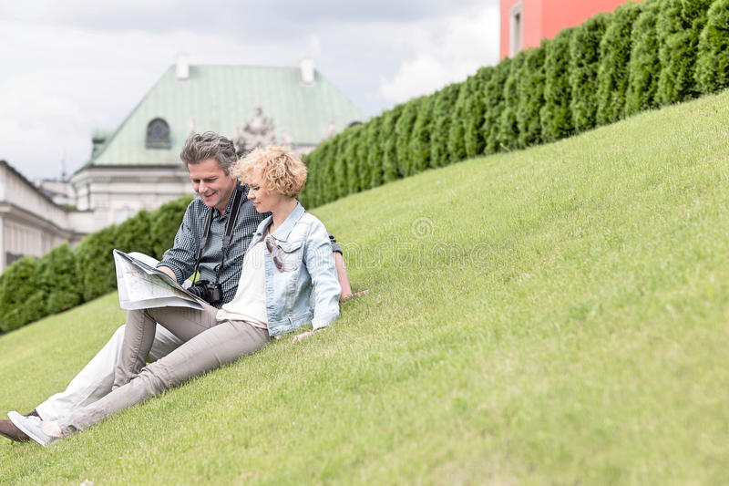 Middle-aged couple reading map while sitting at park stock photo