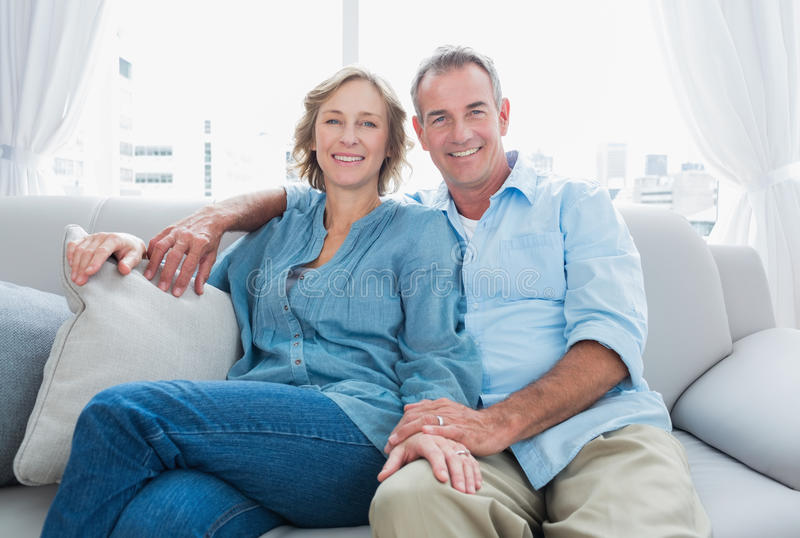 Middle aged couple relaxing on the couch. Smiling at camera at home in the living room stock photography