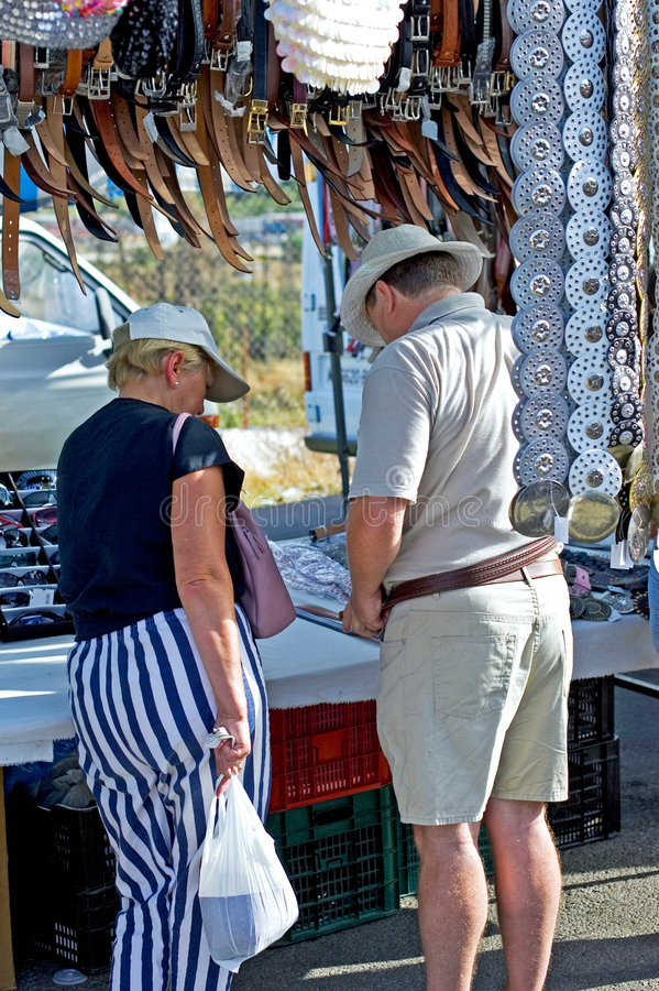 Middle aged couple shopping for a belt in a Spanish market stock photo